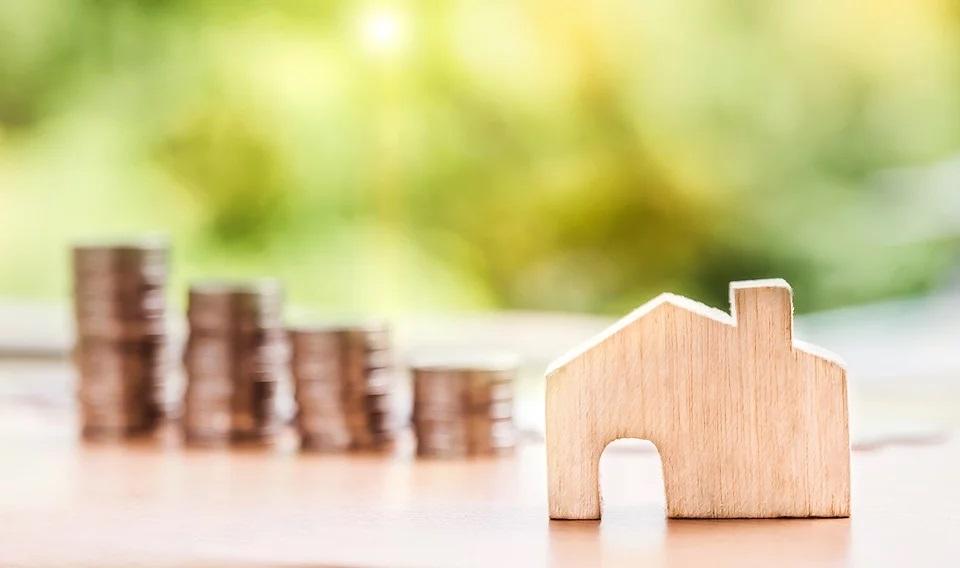 Un modellino di casa in legno con monete impilate