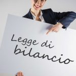 """donna sorridente che tiene in mano un grande cartello bianco in cui c'è scritto """"legge di bilancio"""""""