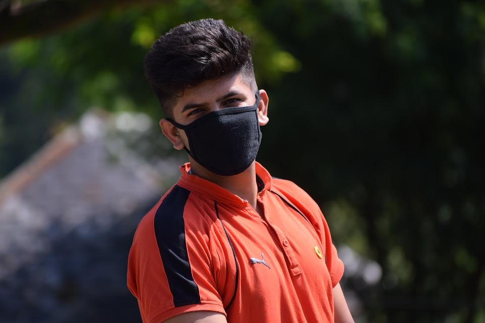Ragazzo con maglia rossa che indossa una mascherina nera per proteggersi dall'inquinamento